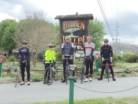 Photo of a group of guests with thier bikes near the Hidden Valley Motel sign